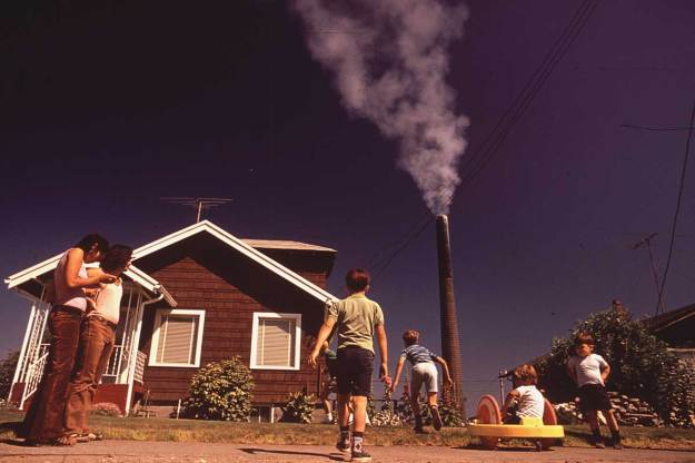 Children play in yard of Ruston home, while Tacoma smelter stack showers area with arsenic and lead residue, August 1972