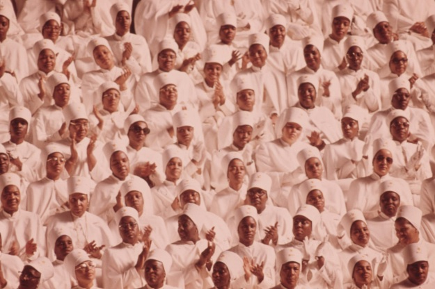 Black muslim women dressed In white applaud Elijah Muhammad during the delivery of his annual savior's day message In Chicago.