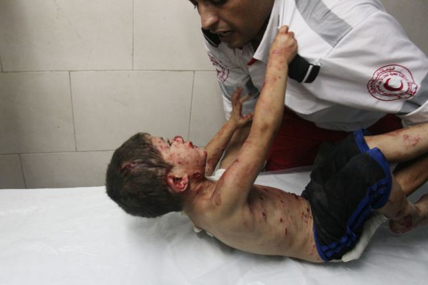 Palestinian medic tries to comfort a wounded boy at Shifa hospital in Gaza City, northern Gaza Strip, early Friday, July 18, 2014 © Ezz al-Zanoun